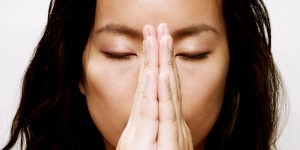 young asian woman with hands clasped in prayer